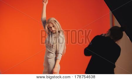 Fashion photo backstage: blonde model and photographer - photo session in studio, red background