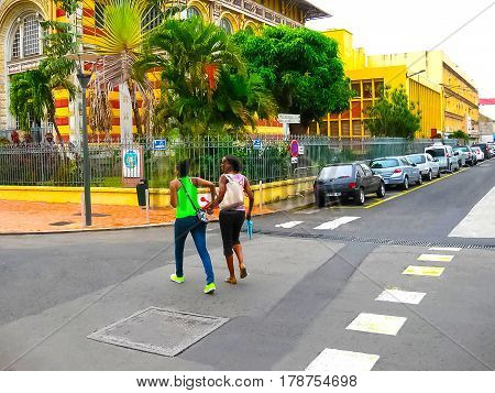 Fort-de-France, Martinique - February 08, 2013: The local girls going to Schoelcher library at Fort-de-France, Martinique on February 08, 2013. This building was first erected in Paris, than transported and rebuilt in Fort de France, West Indies, in 1893.