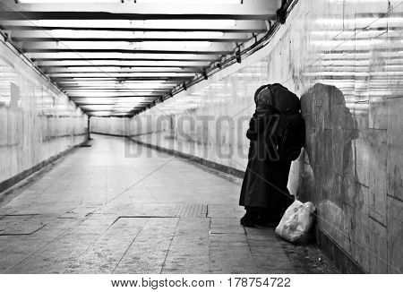 a homeless stands at the tunnel and asked for alms