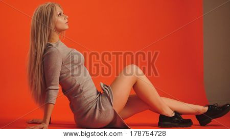 Beautiful blonde girl in cocktail dress posing for photographer - fashion backstage, red background