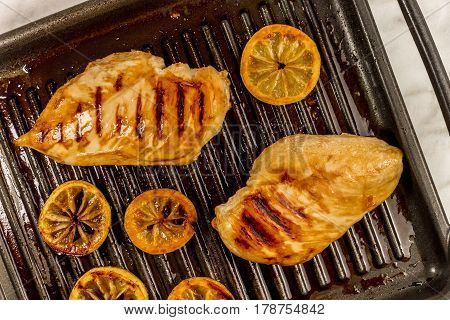 An overhead photo of grilled chicken breasts on the pan, with lemon slices