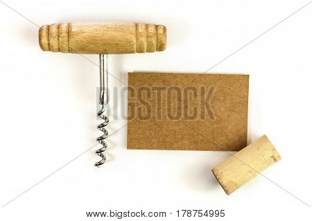 A photo of a brown kraft business card with a cork and a corkscrew, shot from above on a white background. Design template for a wine list or tasting invitation
