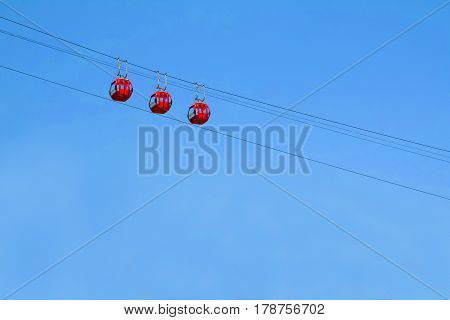 Panoramic lifts in the sky. Sightseeing Elevator on cables high. Red booths for tourism and air travel on the planet.