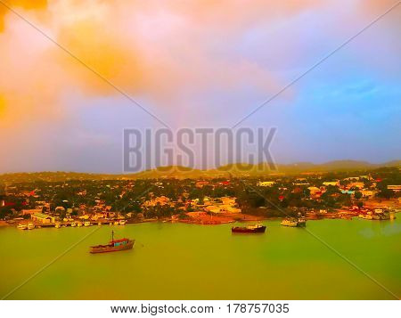 Small yellow boats and many colorful buildings on the coast of Martinique. Image blurred in postproduction