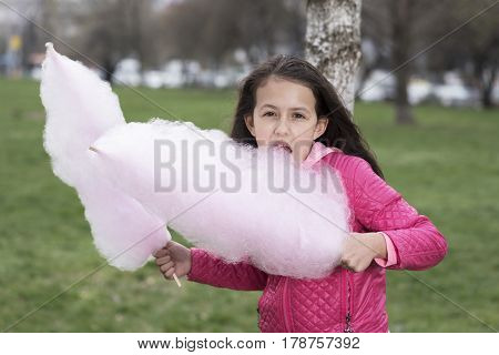 Cute girl eating pink cotton candy in the park