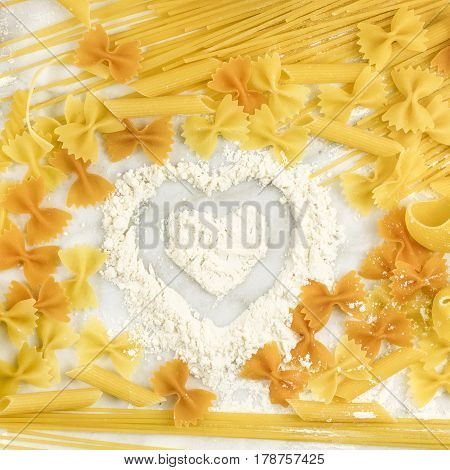 A square photo of various types of pasta on a white marble table, with a heart drawn in flour