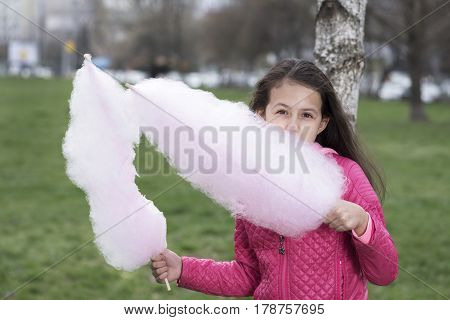 Horizontal picture of cute preteen girl eating cotton candy
