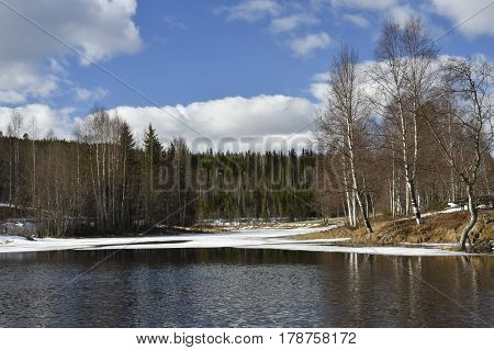 Calm water on a little lake with some ice left blue sky with clouds in background picture from the North of Sweden.