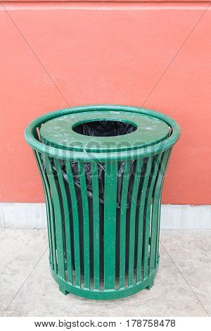 green iron trash can against the wall