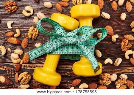 Dumbbells, nuts and measuring tape. The importance of healthy living.