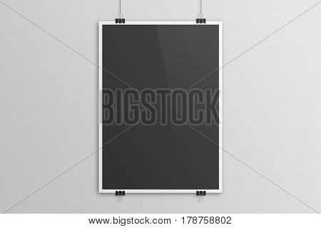 Black poster mock up with white frame on grey sandstone background. Paper clip hanging method.