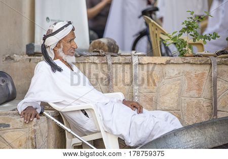 Nizwa Oma 24th March 2017: old Omani man selling old copper cooking dishes at the market