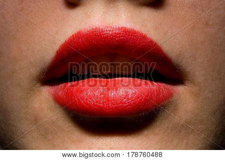 Makeup. Sexy slightly opened girl lips painted with red lipstick.