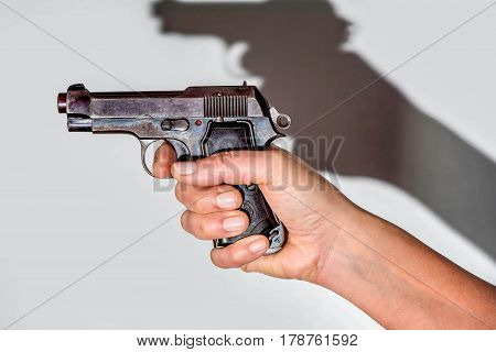 Woman holding beretta gun in her hand and aiming