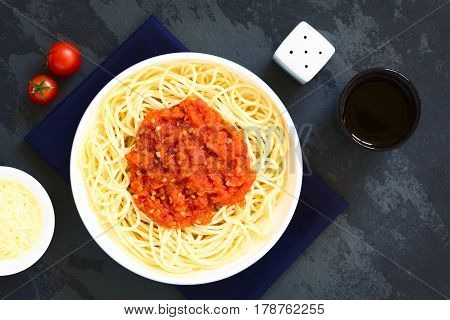 Traditional Italian Spaghetti alla Marinara (spaghetti with tomato sauce) in bowl with red wine and grated cheese on the side photographed overhead on slate with natural light