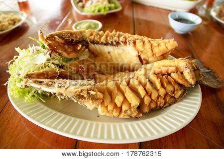 Thai food Deep Fried Fish with Fish Sauc(Pla Tod Num-pla)Fish sauce fried sea bass.