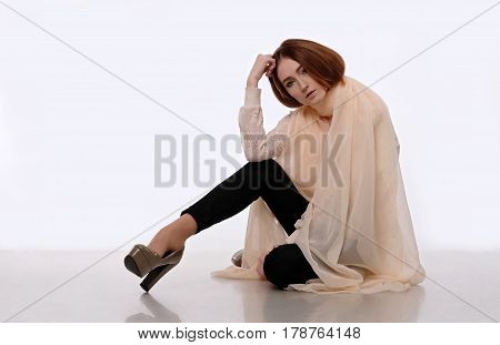 Young girl in beige translucent scarf sits on the white floor. She looks in the camera. Her elbow rests against a bent knee. Emotion: lovely, tenderness, grace. Isolated on white background.