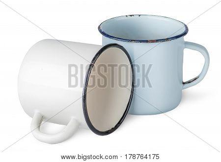 Two old enameled mugs beside isolated on white background