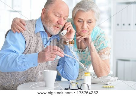 Portrait of an elderly couple with pills and thermometer on the phone with doctor or pharmacy.