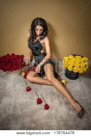 Beautiful brunette woman with bouquet of many red and yellow roses at interior apartment, valentines day.Sensual attractive lady sitting on the floor with a two large bouquet of red and yellow roses
