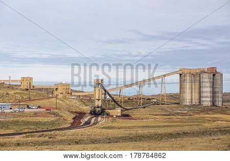 Cement silos at an industrial coal mining site in a spring Wyoming countryside landscape