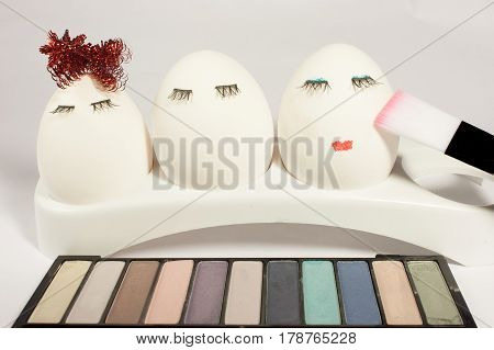 Three eggs with eyelashes in front of a palette of eye shadows make them make-up