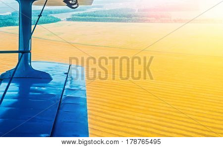 A view of the wing of a turboprop aircraft and a field of corn and wheat in the countryside.