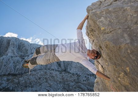 Young man climbing rock wall and hanging above gap. Roao Villanueva del Rosario Malaga