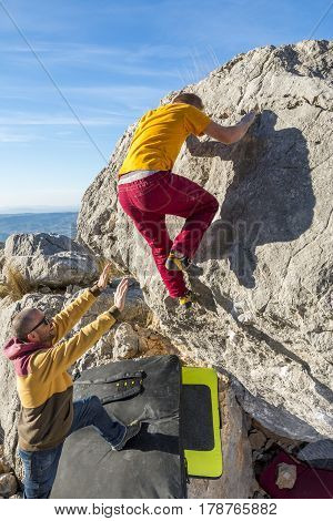 Back view of man climbing rock bouldering. Roao Villanueva del Rosario Malaga.