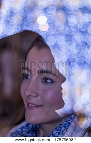 Double exposure of young woman looking away and face silhouette with christmas lights