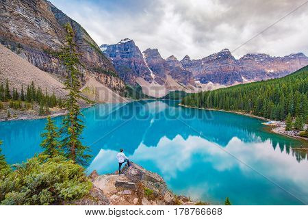 Man takes in the breathtaking view at Moraine Lake in Banff National Park, Canada
