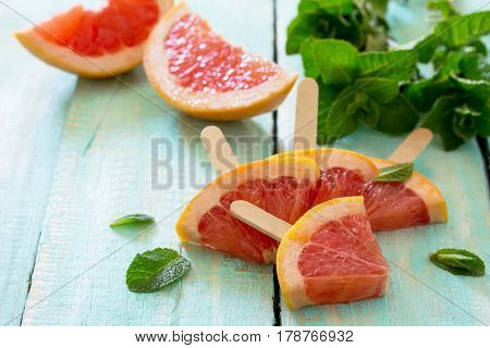 Summer Background. Slices Of Red Grapefruit Popsicle On A Vintage Wooden Background.