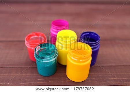 Multicolored plastic cans with paints. Artist workplace background. Art tools. Paints background. Colorful artist palette. Soft toned. Creativity, visual art concept. Art and craft. Closeup