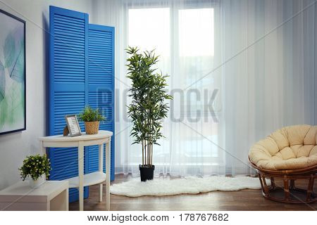 Light room interior with blue folding screen