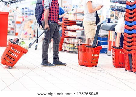 People at supermarket checkout holding red shopping trolley - Concept of everyday life inside department store