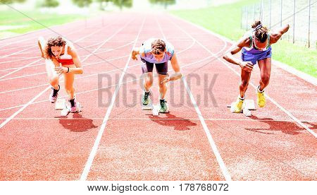 Row of multiracial runners at start grid on red athletics track - Professional sprinters explosive speed training - Concept of preparation for sports events and competition