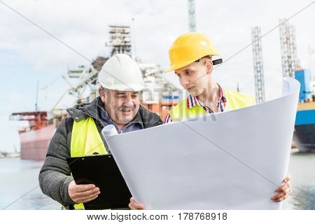 Shipbuilding engineer discusses documents with a student. Experienced worker wearing white safety helmet explains technical issues to a manual labourer. Shipyard.
