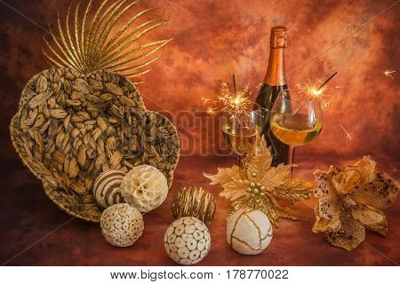 Still life with Christmas decoration champagne and sparklers on a warm background