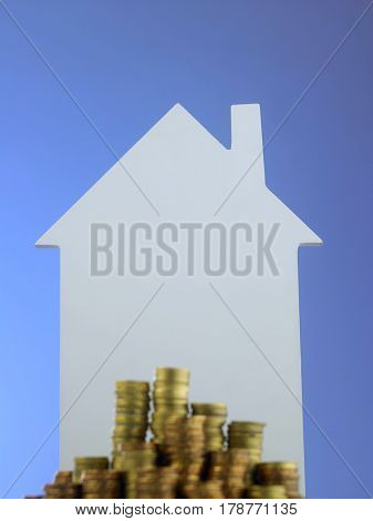 Few stacks of golden coin with house shape as background