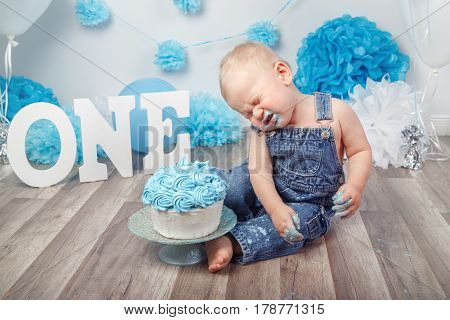 Portrait of cute adorable crying sad Caucasian baby boy in jeans overall celebrating his first birthday with gourmet cake letters one and balloons cake smash in studio