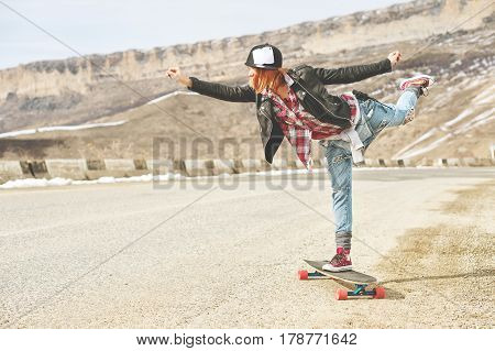 Stylish happy Young girl in a cap and denim overalls balancing in the middle of a mountain road on a longboard in balance