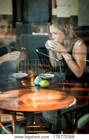 Girl Sat In The Window Of A Coffee Shop Drinking Coffee