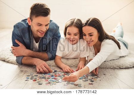 Charming little girl and her beautiful young parents are doing jigsaw puzzle and smiling while lying on the floor at home