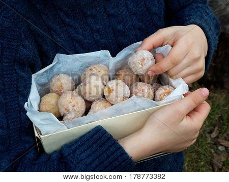 Box Of Oat Donuts With Cinnamon And Powdered Sugar. Street Food. Round Fritter