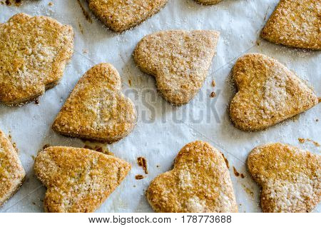 Cookies in the form of hearts on baking paper, top view.
