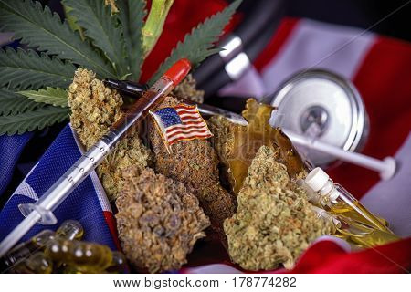 Cannabis buds and american flag with some oil extractions and leaves - veteran themed medical marijuana concept