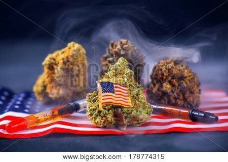 Cannabis buds and american flag with some oil extraction and smoke - veteran themed medical marijuana concept