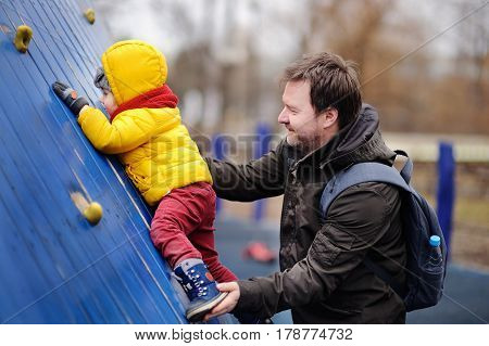 Happy little boy with his father having fun on outdoor playground. Spring and autumn active leisure for kids.