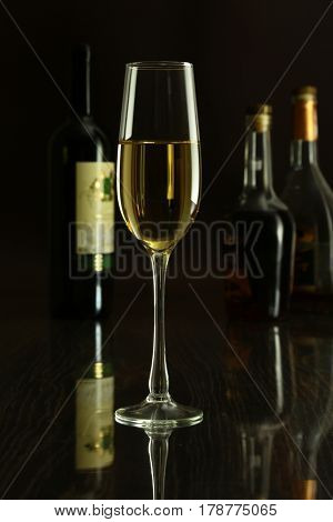 Wine glass and Bottle on a black mirror background.