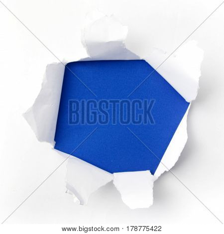 torn white paper on blue background. Cocept for autism awareness day.